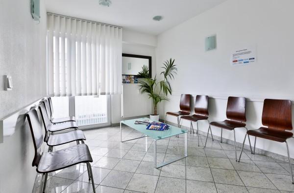 Das Wartezimmer unsere Zahnarztpraxis im 5. OG. Das Zimmer ist schön hell. Die Stühle sind braun.